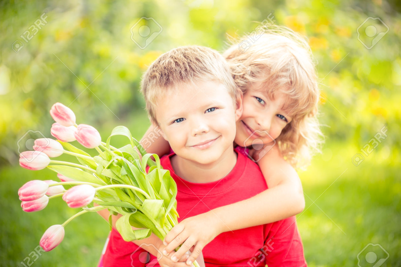 Happy children with bouquet of flowers. Boy and girl against green background. Spring family holiday concept. Women's day